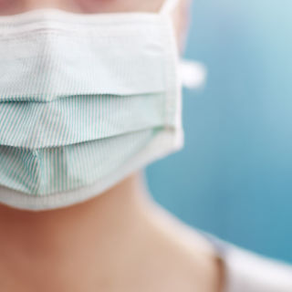 young woman in medical face protection mask indoors on blue background. Sick person